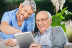 caregiver and elder using tablet